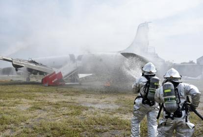 Dos bomberos combaten con agua el incendio generado en la aeronave, durante el simulacro realizado.