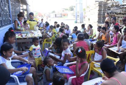 Al menos cincuenta personas, entre adultos y niños, cantan bingo en el sector Tres Postes del barrio Rebolo.