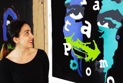 La artista Jocelyn Montero posando junto a una de sus pinturas.