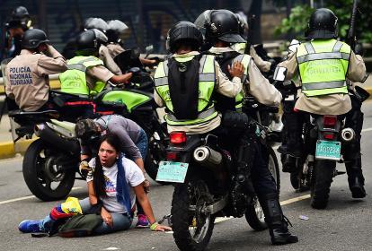 Dos manifestantes en medio de las protestas contra el gobierno de Nicolás Maduro.