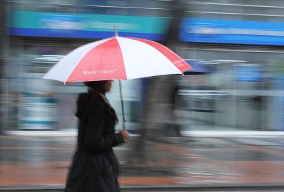 Una mujer camina bajo la lluvia en la capital del país.