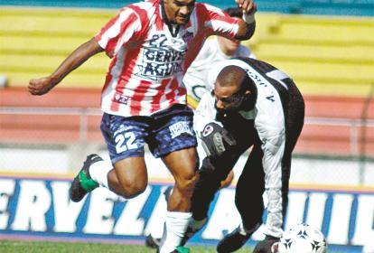 Néstor 'Palmira' Salazar con la camiseta del Junior eludiendo al portero Agustín Julio, para luego marcarle.