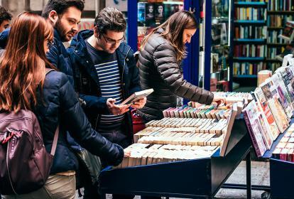 Compradores buscando entre los distintos libros de un estante de segunda.