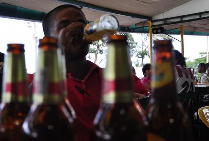 Un hombre consume cervezas en una tienda de la ciudad.