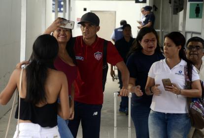 Luis Díaz se toma fotos con dos hinchas que lo abordaron a su llegada al aeropuerto Ernesto Cortissoz.
