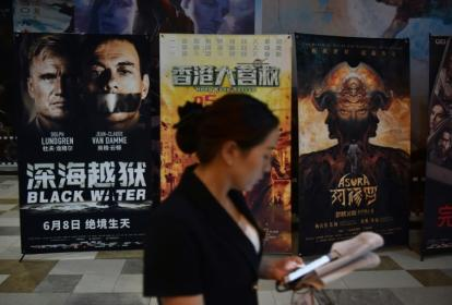 Mujer asiática cerca de las carteleras de cine.