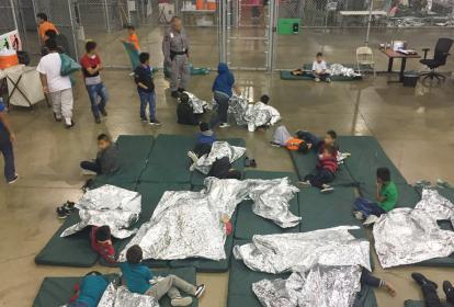 Algunos pequeños aparecen con sus padres en un centro de inmigrantes.