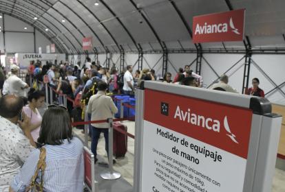 Viajeros realizan 'check in' en el módulo de Avianca para poder abordar el avión.