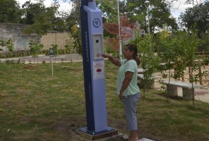 Mujer toca el poste interactivo de seguridad.