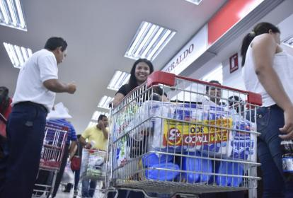 Mujer con un carro de compras en un supermercado.