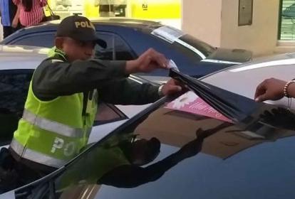 Policía cubre propaganda en un carro.