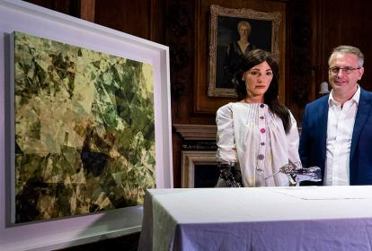 Ai-Da, vestida con una bata, junto a su artífice y dueño de la galería, el comerciante de arte Aidan Meller.