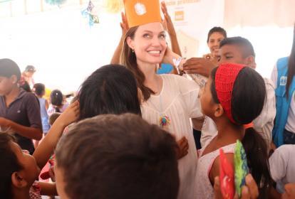 La enviada especial de la ACNUR, la actriz Angelina Jolie, juega con niños en un asentamiento en Maicao que le pusieron una corona de cartón.