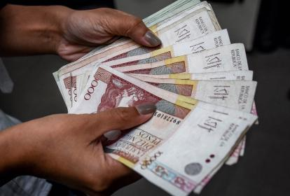 Una persona cuenta varios billetes de diferente denominaciones.