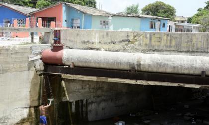 Un residente del sector aprovecha la fuga para recoger agua y bañarse.