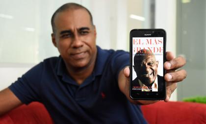 Fernando Perea Sánchez muestra en su celular la portada del libro sobre su papá.