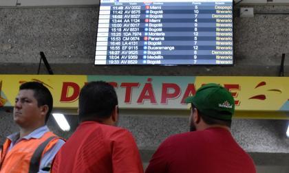 Dos personas aprecian la pantalla del estado de los vuelos en el aeropuerto Ernesto Cortissoz.