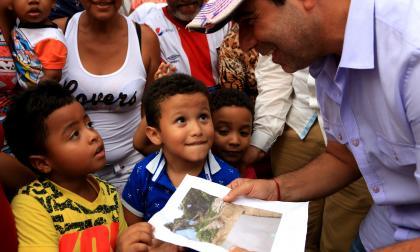 El alcalde de Barranquilla, Alejandro Char, muestra a los niños un proyecto.