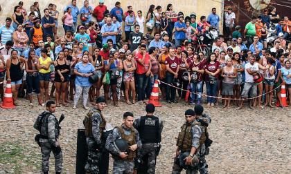Familiares y amigos de varios reclusos de la cárcel en Itapaje (Brasil) esperan frente a una zona acordonada por la Policía noticias sobre los internos luego de los enfrentamientos de este lunes.