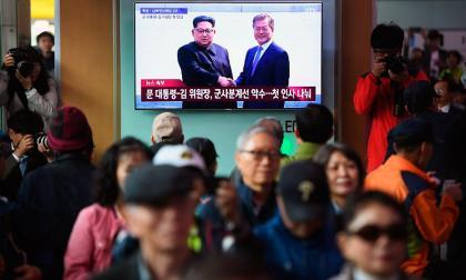 Ciudadanos observan el momento del saludo entre el líder norcoreano, Kim Jong-Un y el líder de Corea del Sur, Moon Jae-In.