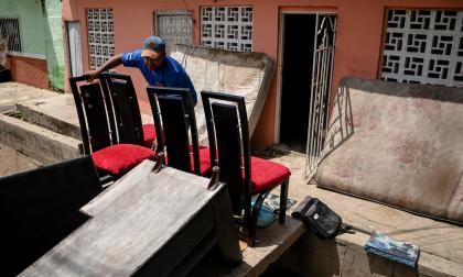 Elkin García pone bajo el sol los muebles que se mojaron tras el desbordamiento.