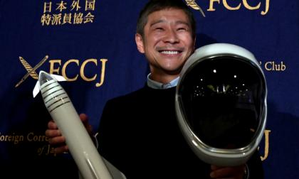 Yusaku Maezawa posa con elementos que representan el viaje que hará a la Luna en el 2023.