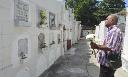 Orlando Esquivia Hernández con un ramo de flores blancas frente a las tumbas.