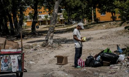 Un hombre en una carretilla busca algún objeto rescatable dentro de la basura en las calles del barrio.