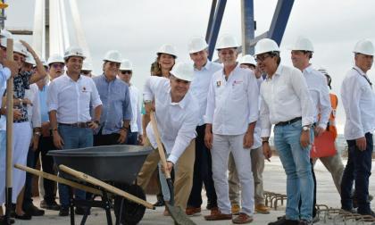 El presidente Duque vacía cemento para la unión final del puente. Lo observan Verano, congresistas, directivos de Sacyr, la vicepresidenta Marta Lucía Ramírez y el director del Invías, Juan Esteban Gil.