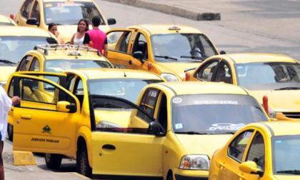 Varios taxis estacionados en una calle esperando pasajeros.