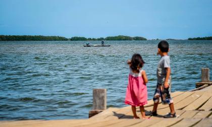 Dos niños observan a un grupo de pescadores mientras adelantan sus faenas en las aguas de la Ciénaga de Mallorquín.