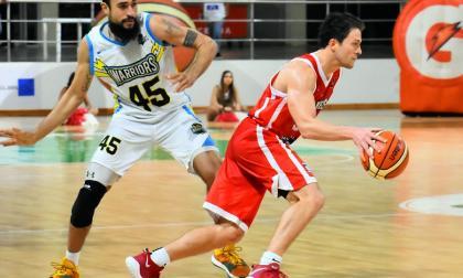 El armador Gianluca Bacci, de los Titanes, lleva la pelota ante la marca de un jugador de los Warriors.