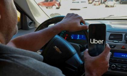 Un conductor muestra el logo de Uber en la aplicación de su celular.
