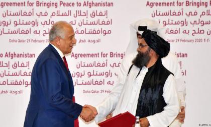El representante especial para la Paz de EE.UU., Zalmay Khalilzad (i), y el mulá Abdul Ghani Baradar (d), se estrechan la mano tras firmar su histórico acuerdo de paz entre Estados Unidos y los Talibanes.