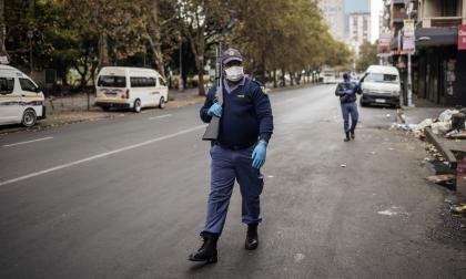 Un policía sudafricano patrulla mientras sostiene un rifle de bomba en Hillbrow, Johannesburgo.