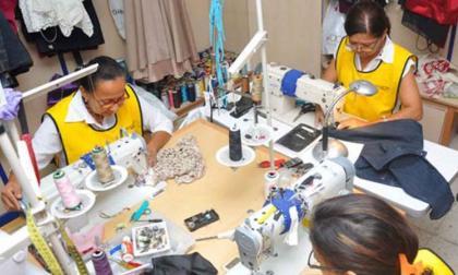 Mujeres trabajan en máquinas de coser.