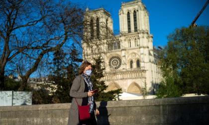 Una mujer caminando frente a la catedral de Notre Dame.