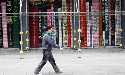 Un hombre pasa frente a un grafiti que simula distintos libros apilados en la ciudad de Madrid, España.