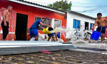 Habitantes del barrio Rebolo sacan agua de sus viviendas luego de que el Arroyo Hospital se desbordara.