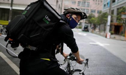 El esgrimista japonés Ryo Miyake montado en la bicicleta con la que realiza los domicilios.