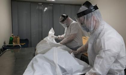Dos trabajadores preparan el cuerpo de un fallecido para cremación.