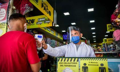 Un trabajador verifica la temperatura de un cliente antes de ingresar a un local.
