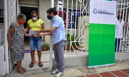 El alcalde Pumarejo entregando las escrituras a una familia en el barrio Galán.