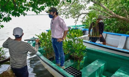 El alcalde Pumarerjo habla con varios de los pescadores que participarán en la siembra de mangles.