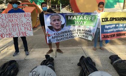 Un grupo de colombianos sostiene pancartas durante una manifestación en contra del expresidente de Colombia Álvaro Uribe.