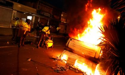 Miembros de la Policía  pasan por una calle donde un tanque de basura fue incendiado durante las protestas de la semana pasada.
