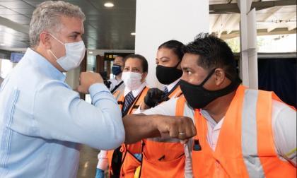 """El presidente Iván Duque saluda """"de codo"""" a varios empleados del aeropuerto Rafael Núñez en el reinicio de las operaciones internacionales."""