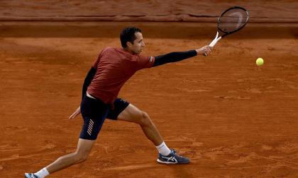 """El colombiano Daniel Galán tratando de responder a los """"misiles de Djokovic""""."""