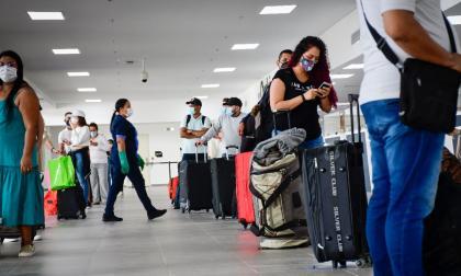 Viajeros hacen fila para hacer el registro.