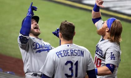 Max Muncy de los Dodgers celebra con su compañero Justin Turner, mientras son observados por Joc Pederson.